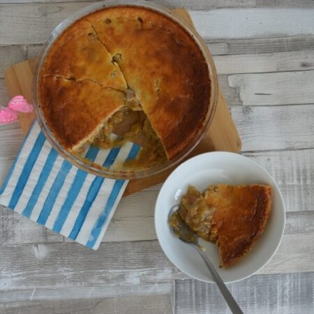 A bowl of rhubarb dessert with a serving dish beside it