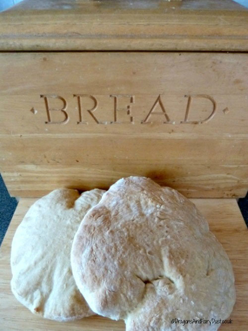 A bread bin with two stotties bedside it.