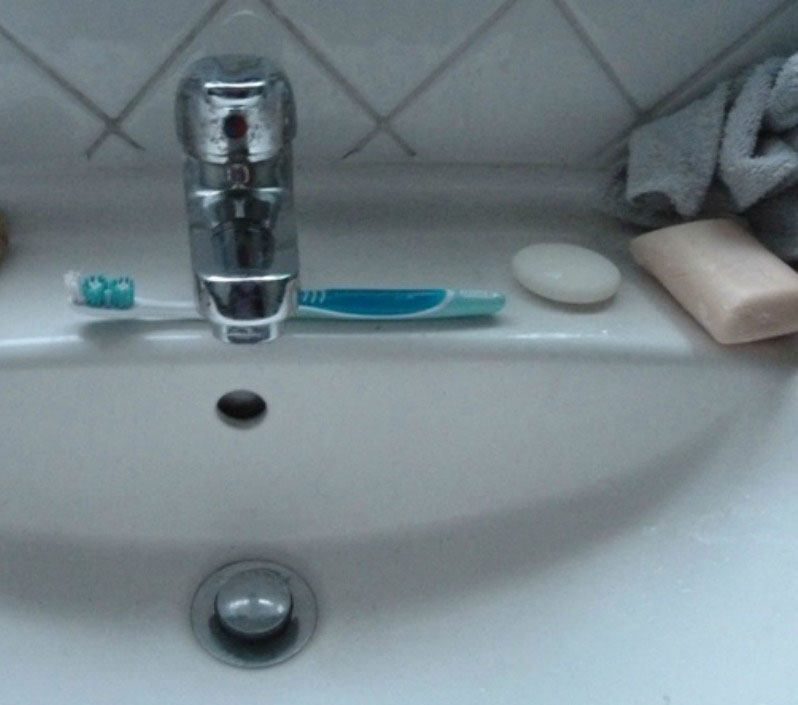 A sink with a toothbrush beside the tap and a bar of soap next to it