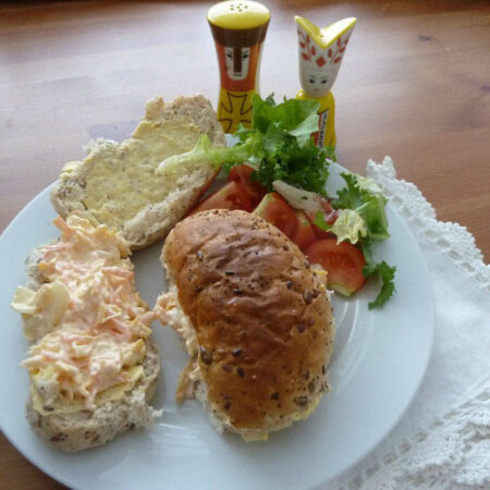 A cheese savoury sandwich on a plate with lettuce. Salt and pepper pots stand behind