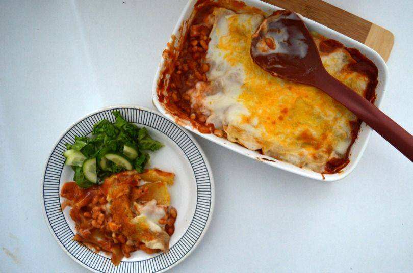 A dish of baked bean lasagne on a table with a serving spoon and a plate beside it with the lasagne on