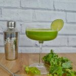 Kale cocktail on a bench with a cocktail shaker and some leaves of kale