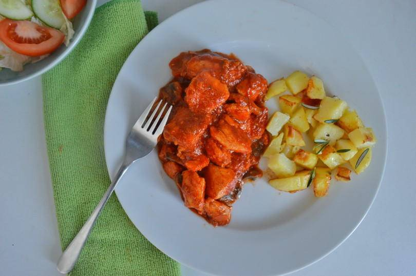 Italian chicken on  a plate beside some fried potatoes