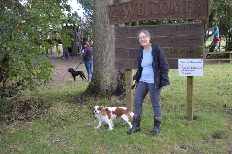 Standing in front of the countryside centre sign at the Rising Sun Country Park with a dog