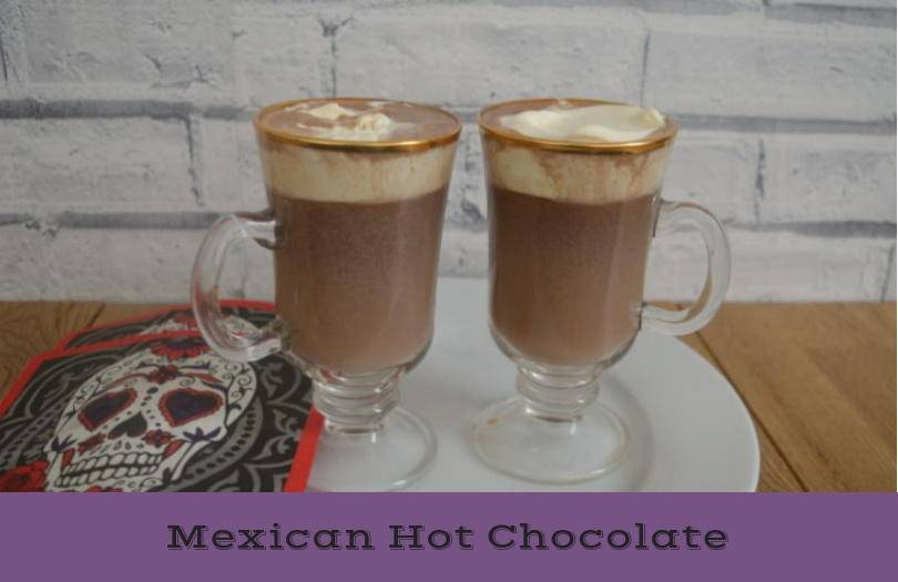 Two tall glasses of mexican hot chocolate with cream topping on a table