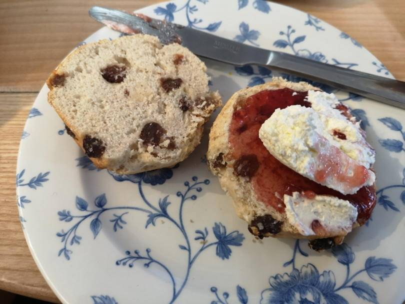 scones on plate, one with cream and jam on top