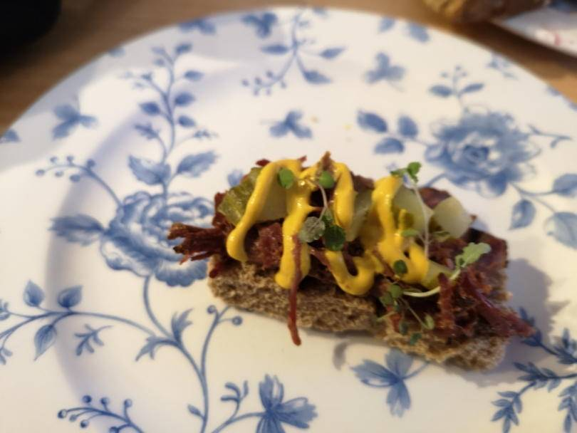 Pastrami and mustard open sandwich on a plate