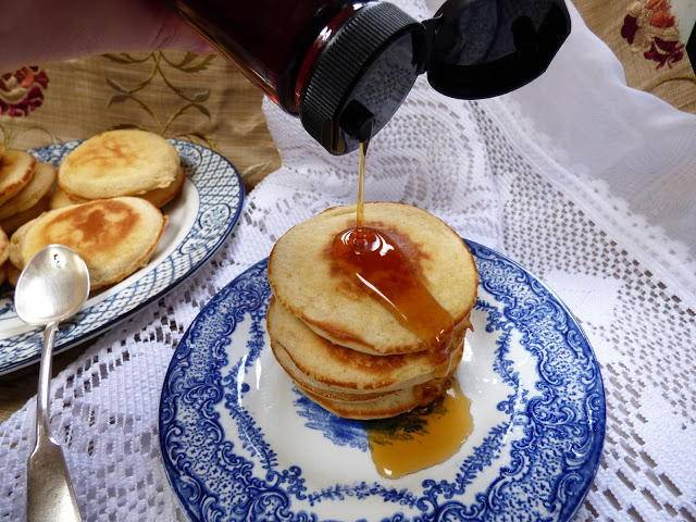 Yukon flapjacks or sourdough pancakes on a plate with syrup being poured over them