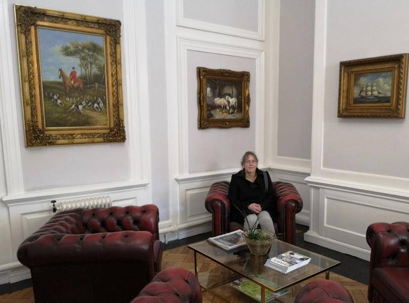 A lady sitting on a seat in Beamish hall hotel entrance with paintings on the wall