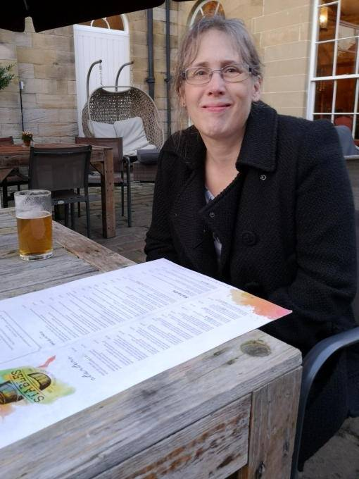 Lady on a seat outside on the stables restuarant terrace with half of beer
