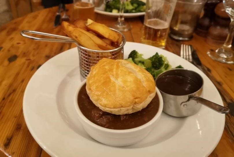 Steak and ale pie with chips and brocolli on a plate at Stables restaurant