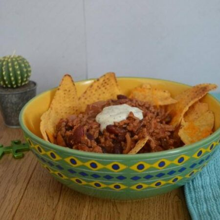 Simple beef nachos in a bowl with sour cream