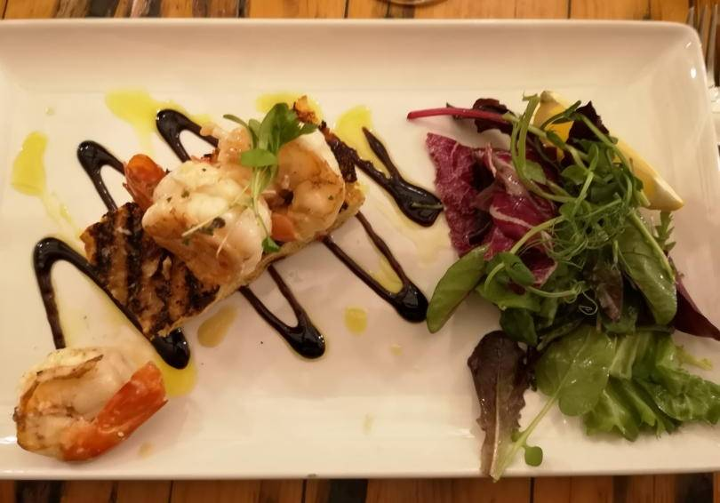 Sauteed king prawns on top of focaccia on a plate with salad and pretty drizzles