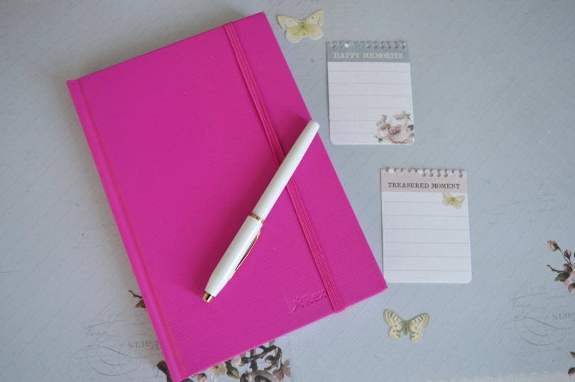 pink notebook on grey background with white pen on top