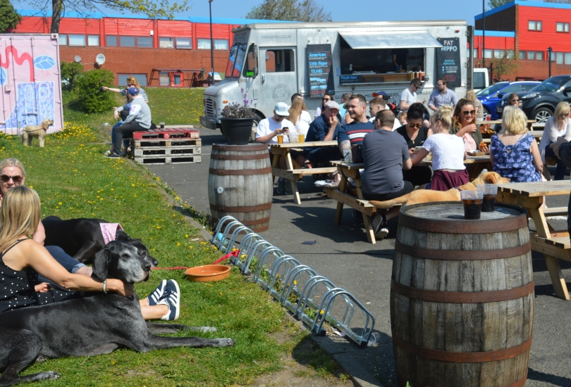 The picnic tables outside Tyne bank brewery with Fat Hippo burger truck in the background and people enjoying the sun