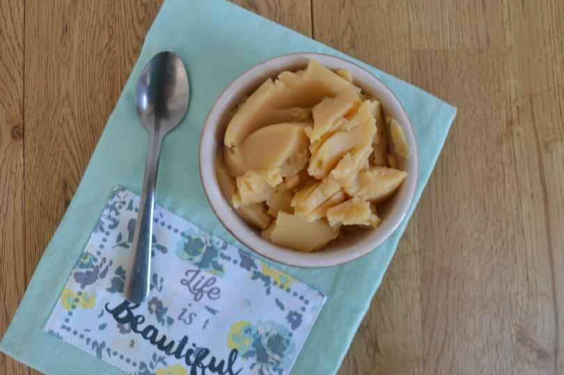 Pease pudding in a bowl on a green cloth with a spoon next to it