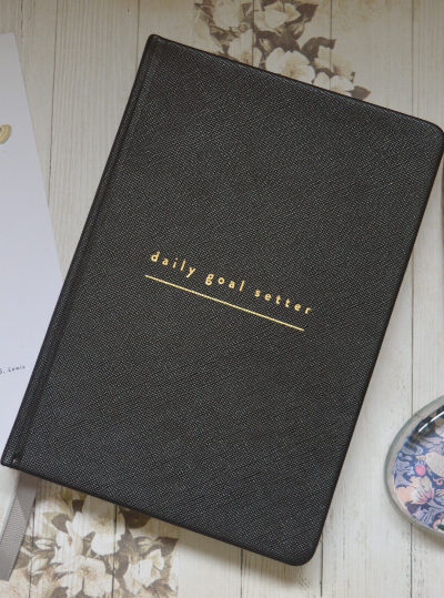 Daily goal setter planner from Mal Paper on a desk with a quill pen beside it