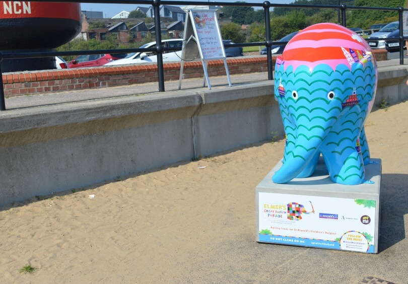 Beyond the sea elmer on the fish quay. He is blue with a red top