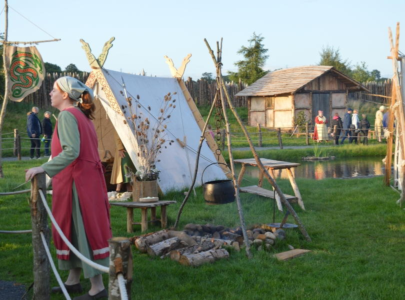 A Viking lady standing in front of a tent and a group of vikings outside a hut in the background in the Viking Village