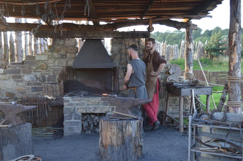 Two blacksmiths beside a forge in a viking hut at the viking village