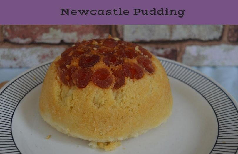 Newcastle pudding - a steamed pudding with a topping of cherries on a plate