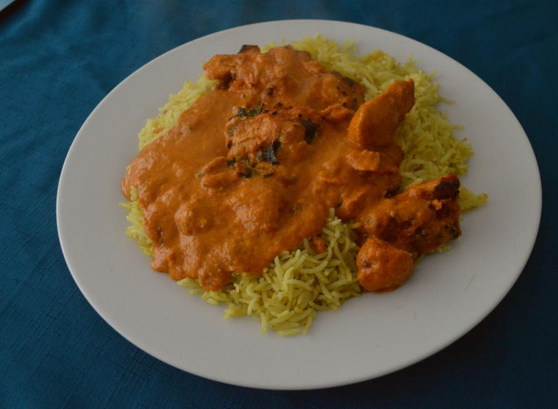 Chicken tikka masala and pilau rice on a plate