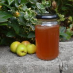 Crab apple jelly in a jar outside with crab apples beside it