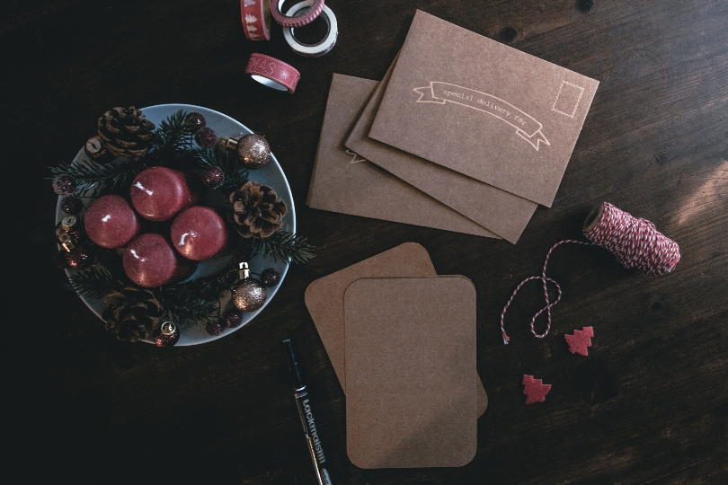 christmas candles and labels on a table with a pen