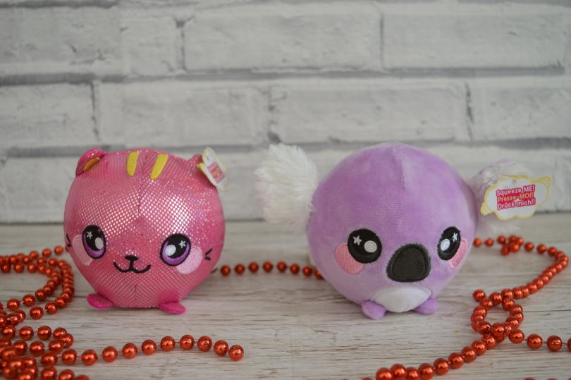 A pink and purple squeezamal plush toy beside each other with a wall behind