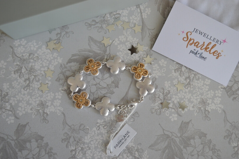 Bracelet with gold and silver flowers on a table