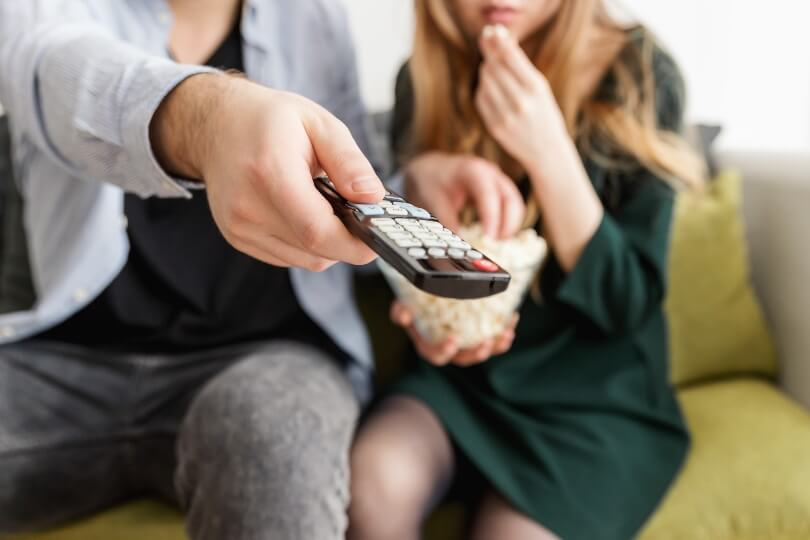 Man holding tv remote control and woman eating popcorn