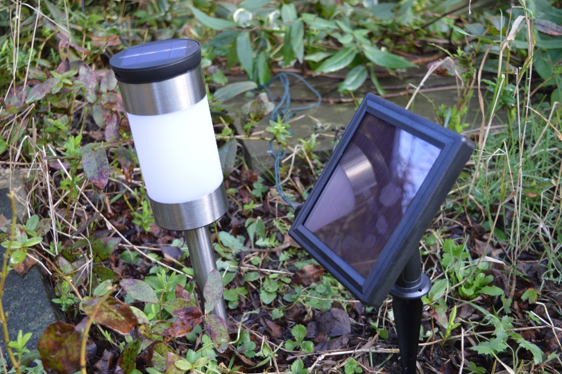 The solar panel for a outdoor solar lights in the garden next to a stake solar light