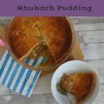 Rhubarb pudding on a table in a dish with the serving dish beside it