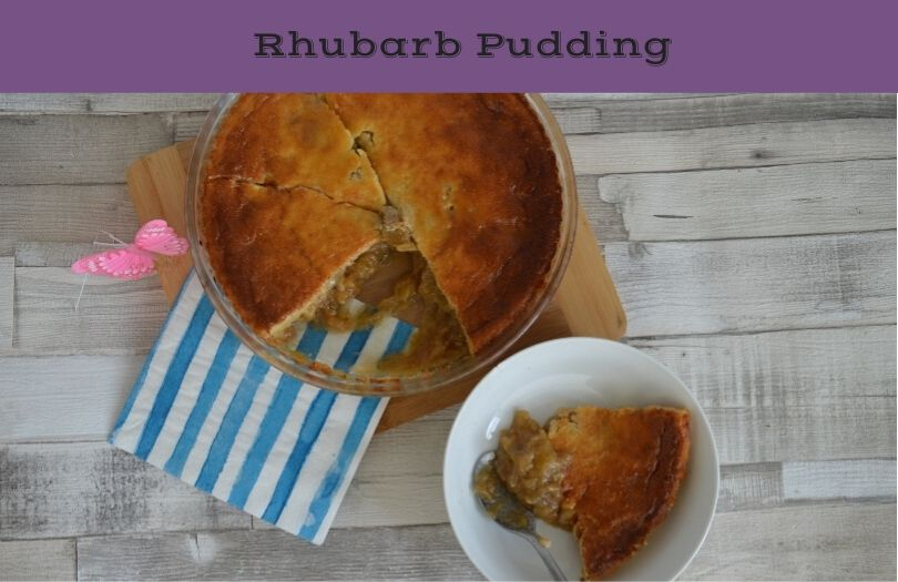Rhubarb pudding in a dish on a table with a full serving dish beside it.