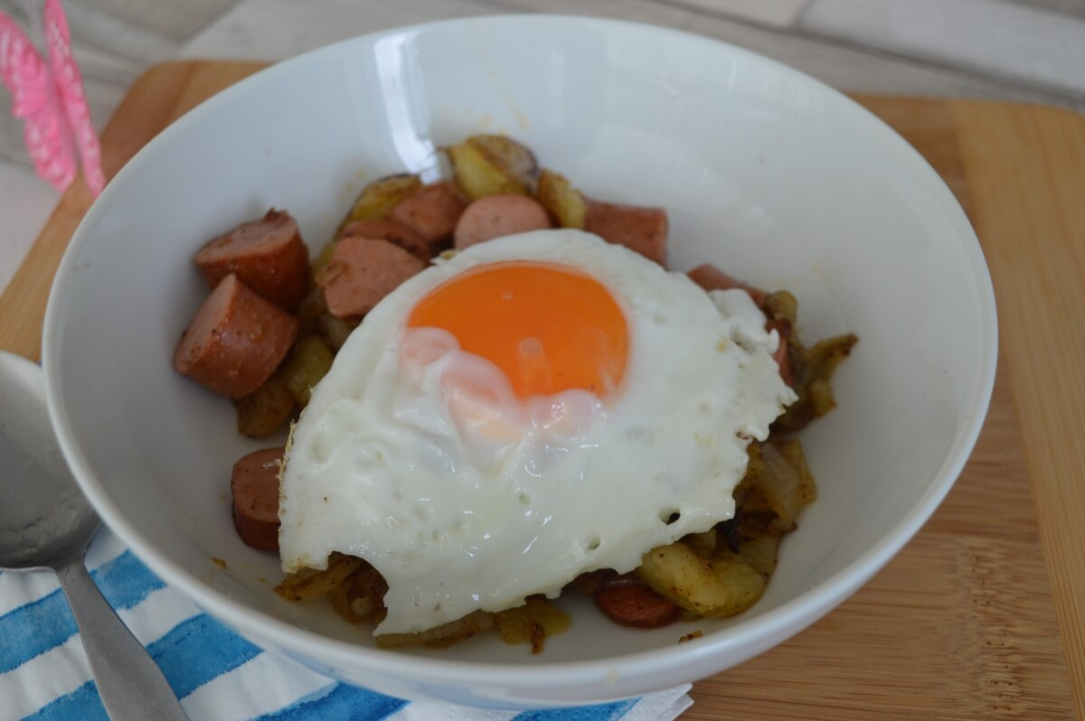 cooked chopped potatoes, onions and hot dogs in a plate with a egg on top
