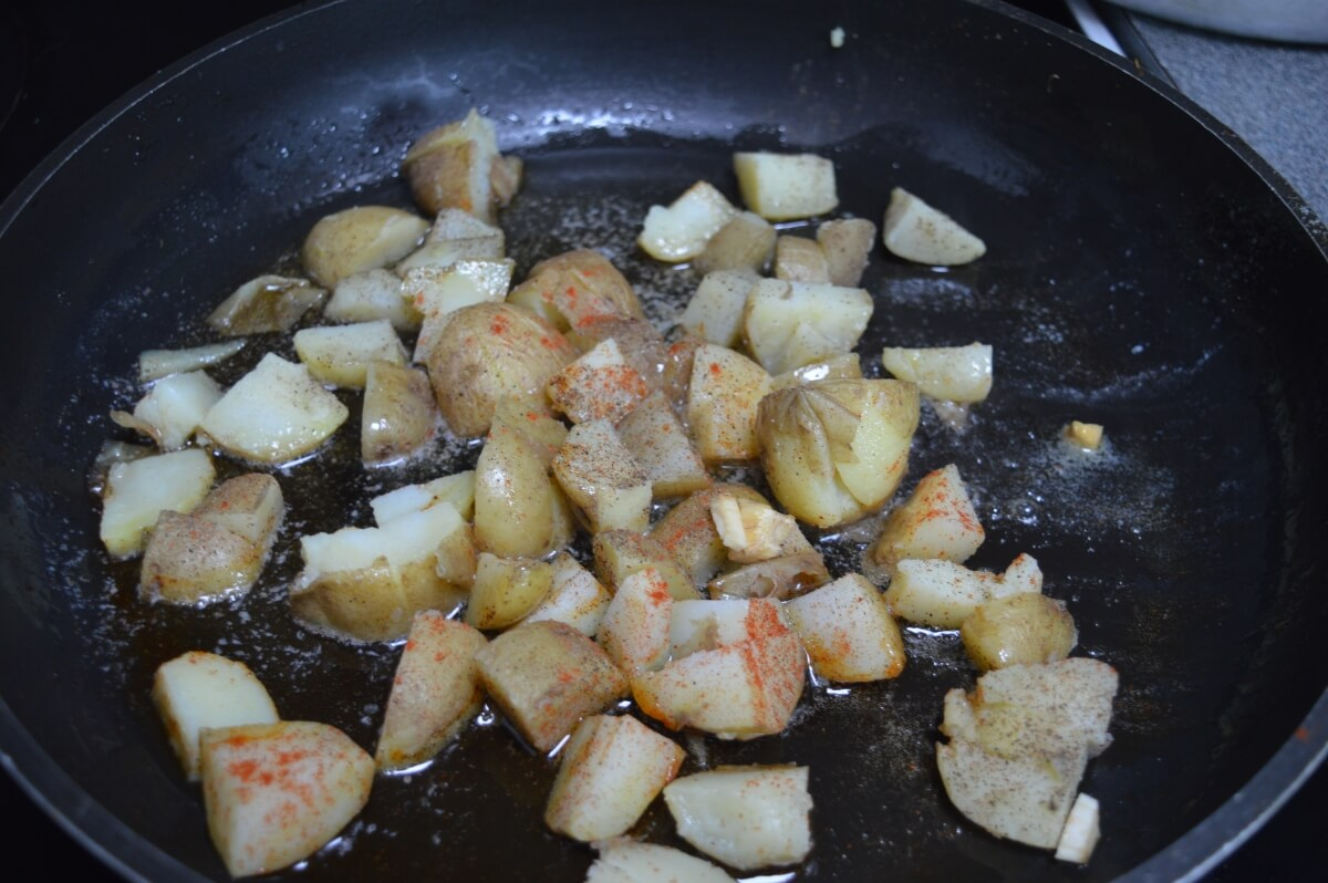 Potatoes onions and garlic in a pan frying