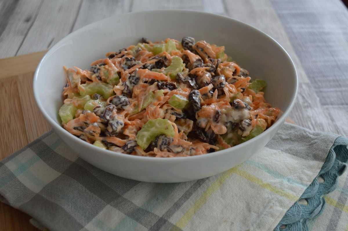 A bowl of salad made with carrots, celery, walnuts, raisins and mayonnaise.