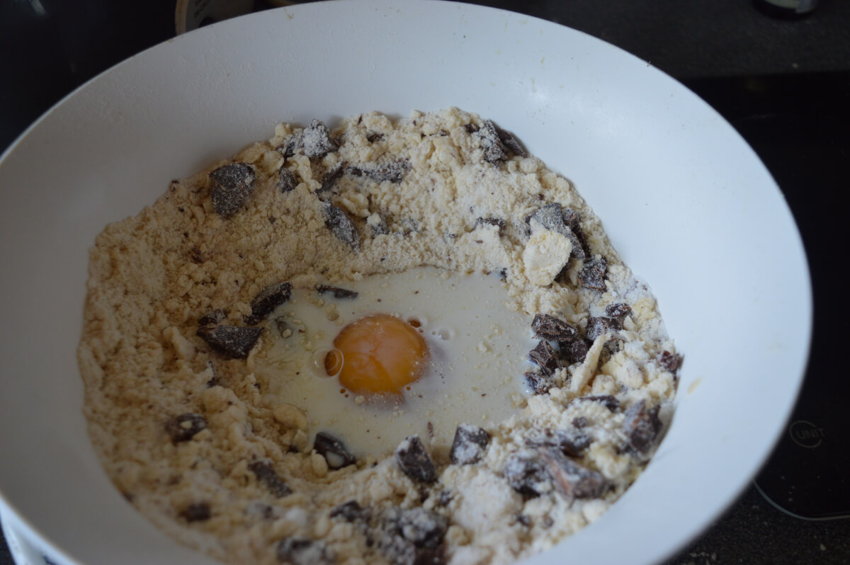 Milk and egg added to a bowl with rubbed in butter flour and sugar with chunks of chocolate