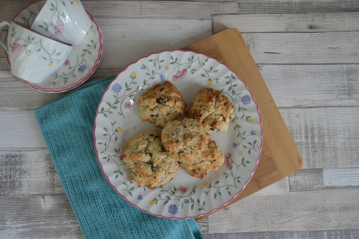 A plate of rock cakes seen from above with tea cups next to them