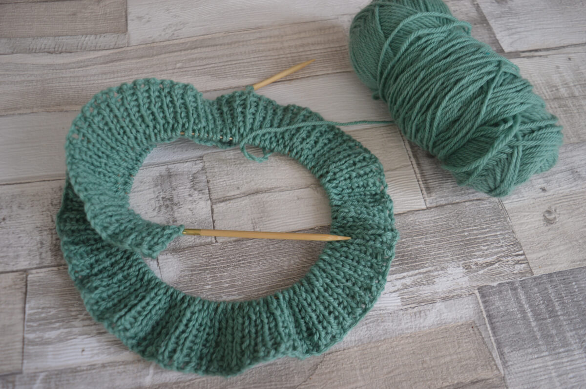 Rows of rib stitch knitting in green wool with the ball of wool beside
