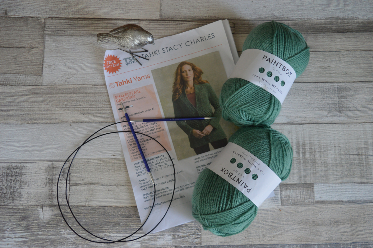 A knitting pattern, knitting needles and two balls of green wool on a wooden floor