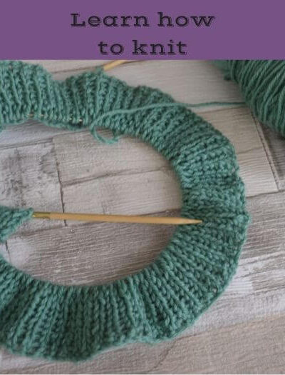 several rows of rib stitch knitting in green wool on planks