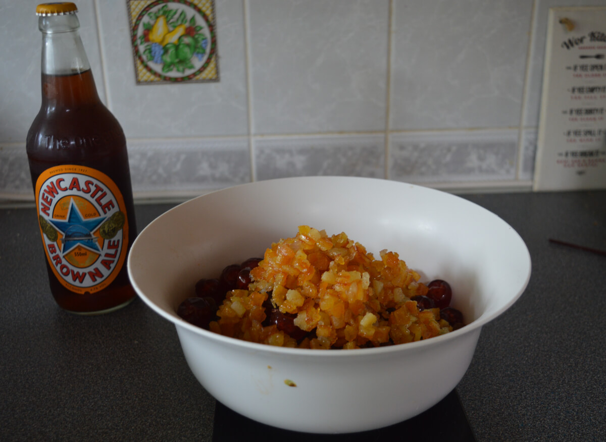 A bowl of dried fruit with a bottle of Newcastle brown ale beside it