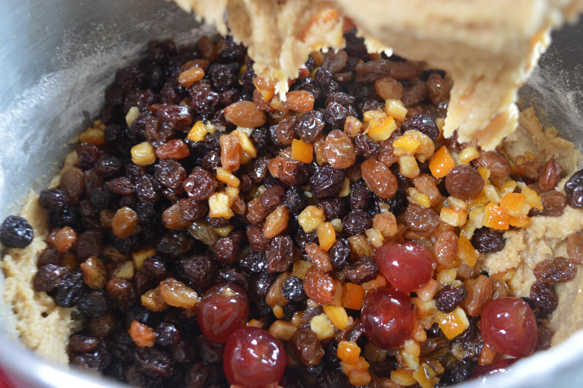 Dried fruit and peel being added to cake mix