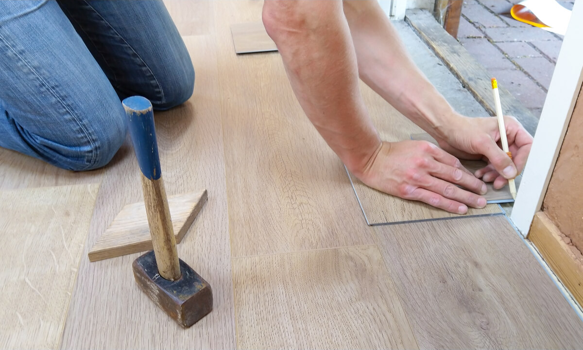 Person measuring floorboards