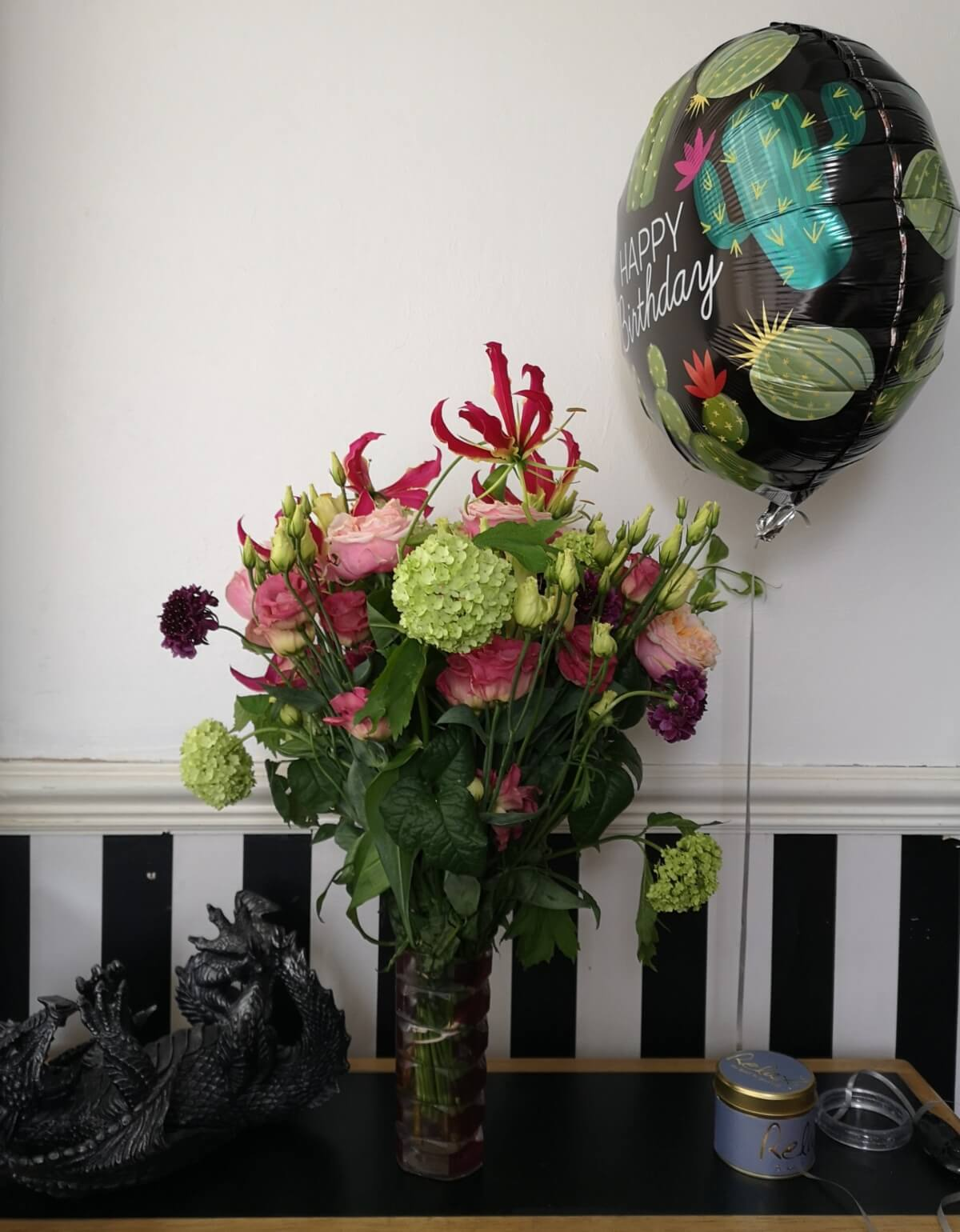 A bouquet of flowers on a table in a vase with a happy birthday balloon next to them