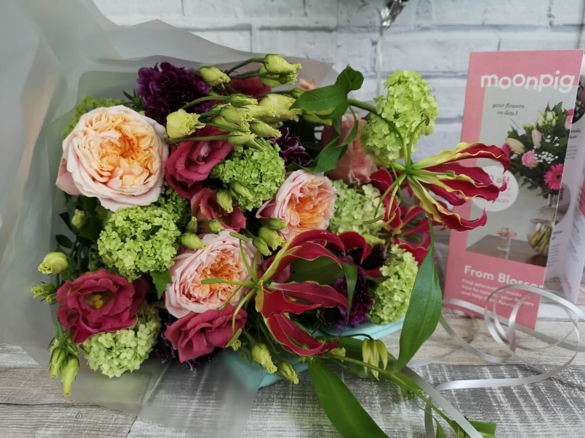 A boquet of flowers from Moonpig in their wrapping on a table with the care leaflet next to them