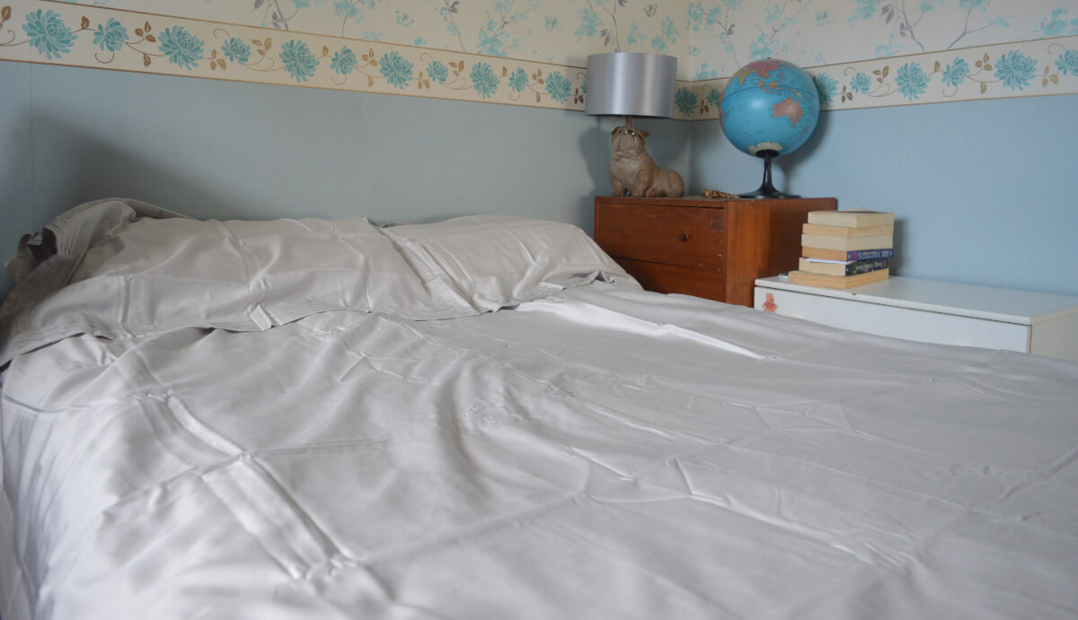 A double bed with grey cotton sheets