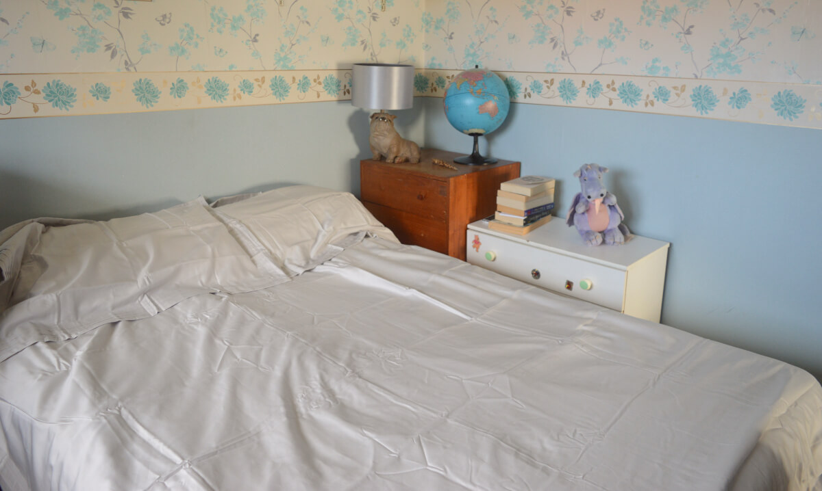 A double bed with grown up grey cotton duvet and pillow cases beside chest of drawers