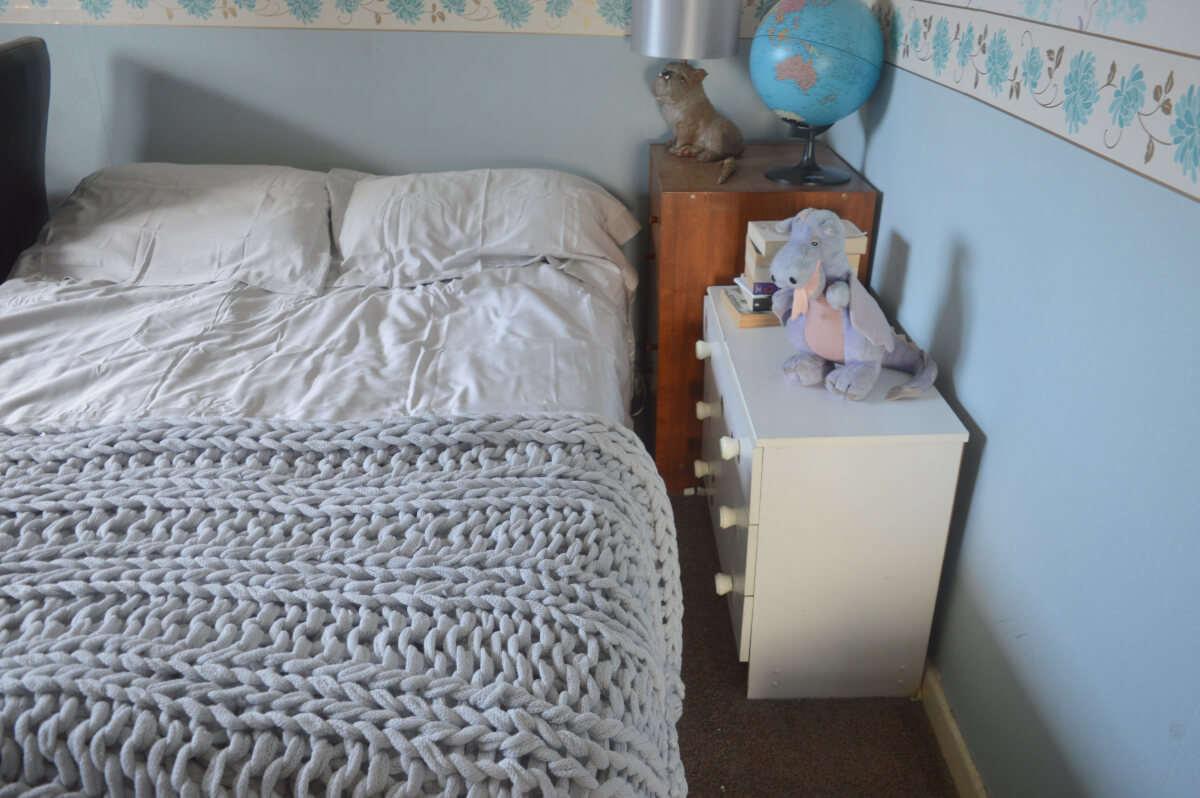 A grown-up bedroom with grey double sheets and a knit throw on the bed beside two chests of drawers